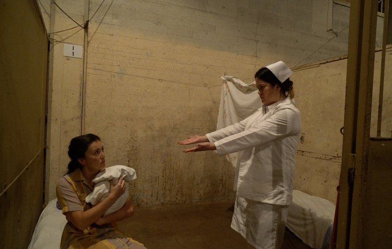 Actors Yoshie Bancroft, left, and Nicole Yukiko perform in one of the stalls in the barn at Hastings Park where over 8,000 Japanese Canadians were detained in 1942. (Mona Stilwell / Bob Baker)