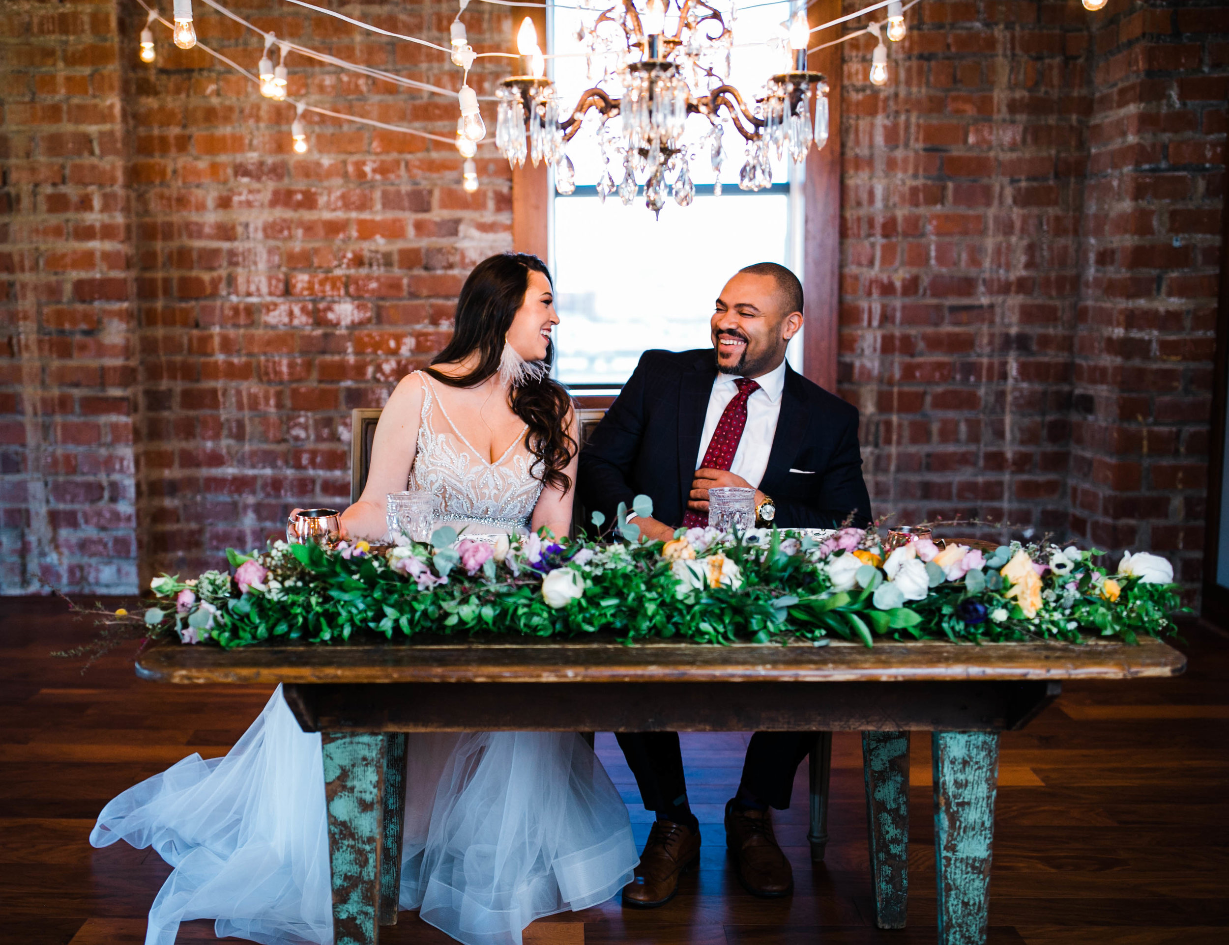 Melia and Julian laugh during their boho-chic, elopement-style shoot with urban vibes. I love the exposed brick, beautiful florals, vintage vibes and natural light here! If anyone wants a warehouse-vibe for their West Virginia wedding or elopement check out Yoga Power! The exposed brick and large windows make for some amazing photos..