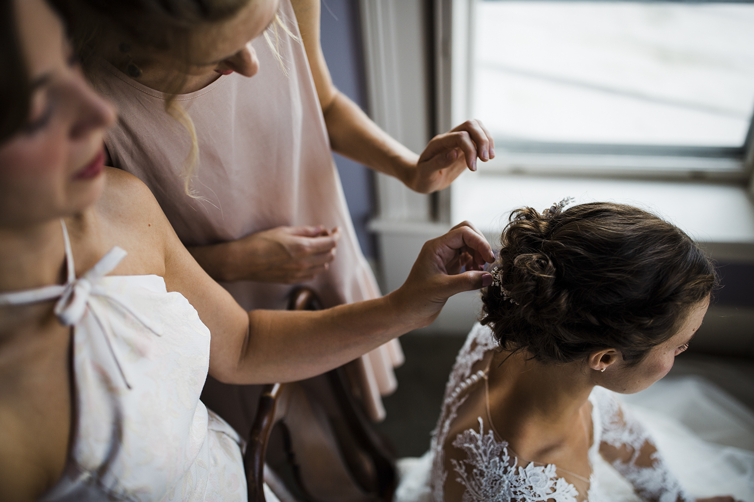 Isabelle's bridesmaids help put the finishing touches on her hair at the Virginia wedding venue the Joshua Wilton House in Harrisonburg