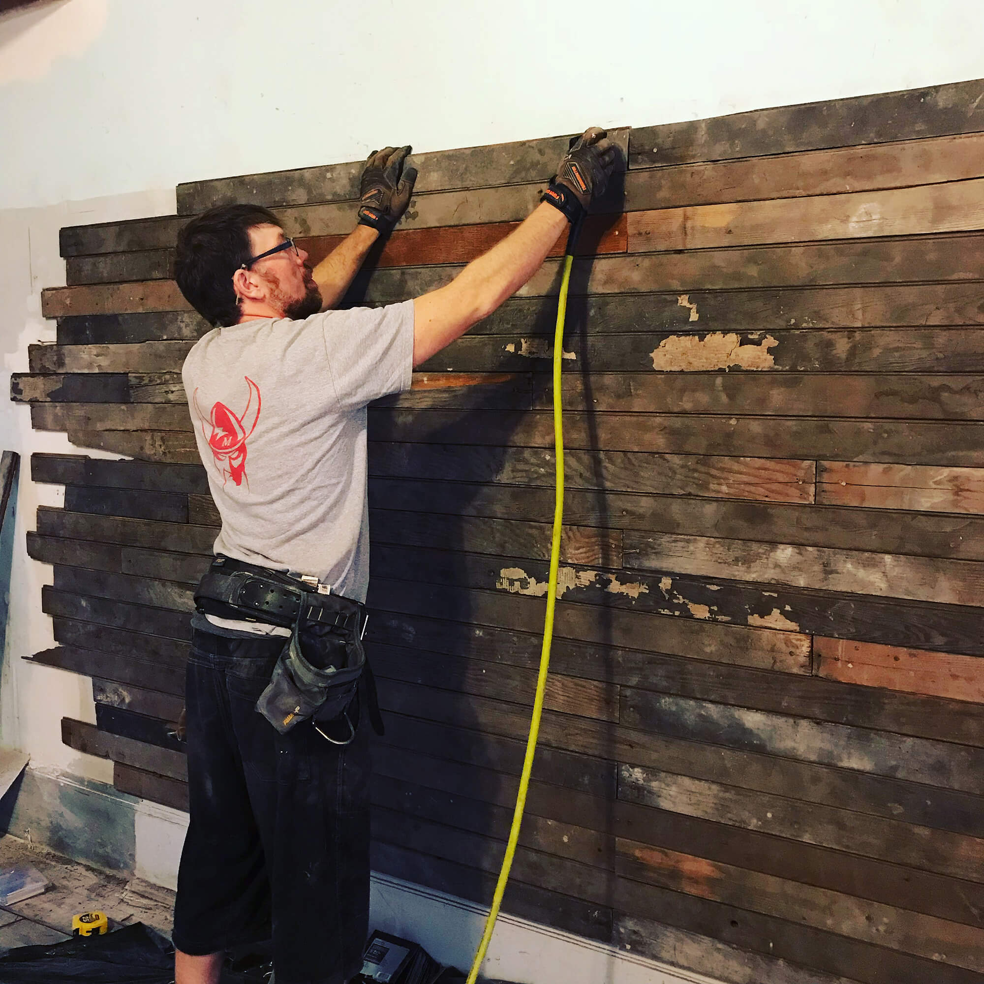 Using wood from a demolished loft to make a reclaimed wood wall.