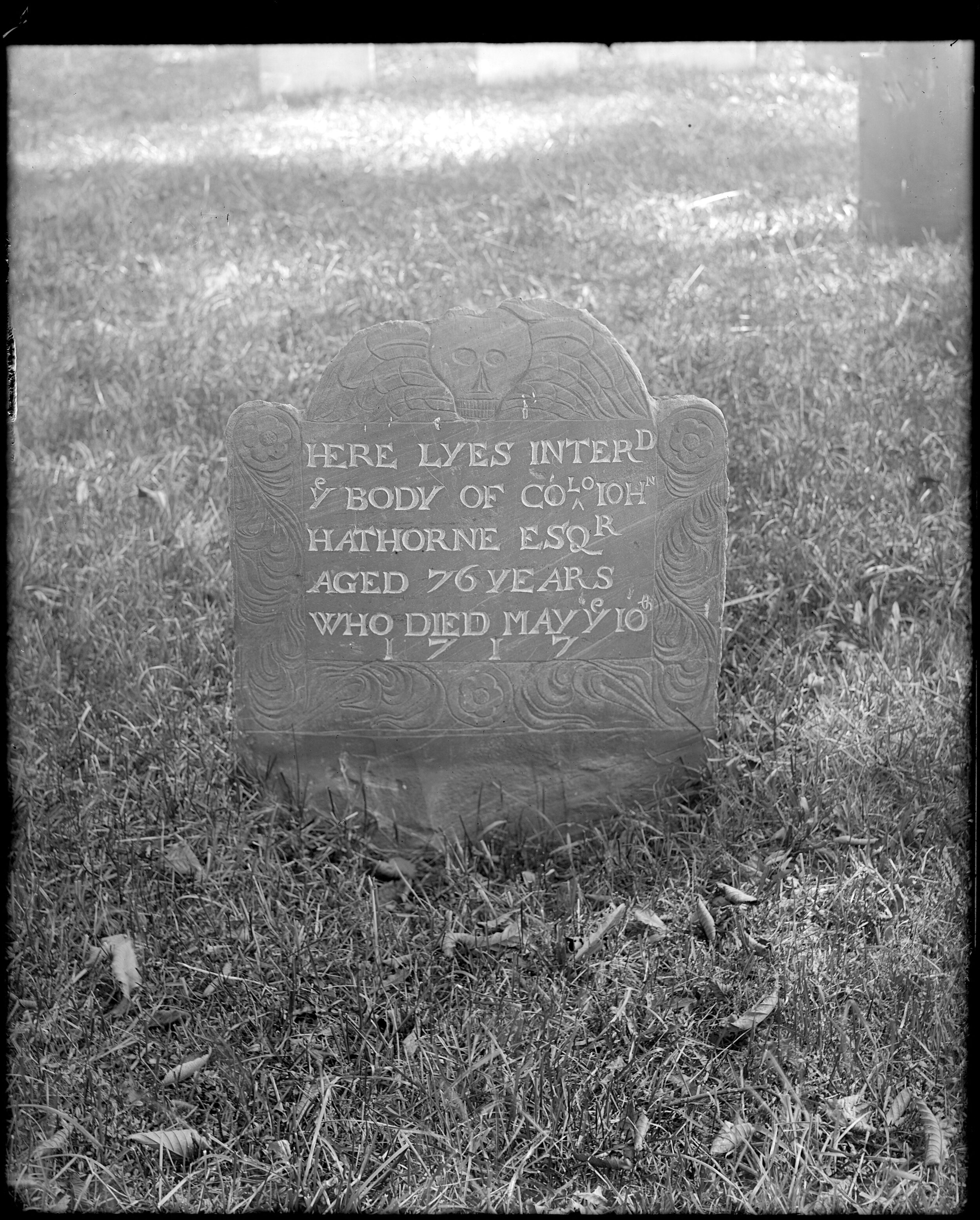 """JOHN HATHORNE   John Hathorne was a judge during the Salem Witchcraft Trials of 1692. His ancestor, Nathaniel Hawthorne, added the """"w"""" to his name to distance himself from the role Justice Hathorne played in the trials. John Hathorne's stone was carved by John Holliman and is now encased in granite.   Frank Cousins, (Monuments, Charter Street, monuments, burying ground, gravestones, Colonel John Hathorne], [1864-1914], Frank Cousins Collection of Glass Plate Negatives, Courtesy of Phillips Library, Peabody Essex Museum, Salem, MA."""