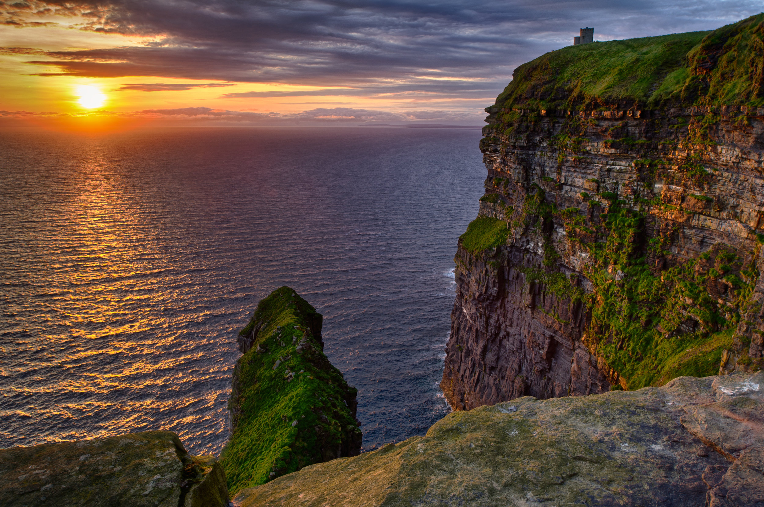 September 9: The BurrenCliffs of Moher - Check out of your hotel this morning and take off on the road to see Co. Clare. Start your day by exploring The Burren, one of Ireland's most unique and photogenic landscapes.  Stretching over 160 square km, the Burren, derived from the Gaelic word Boireann meaning 'rocky place', is one of the most visited attractions in the Shannon region.Aptly named, the karst topography is characterized by its unusual limestone formations, naturally sculpted through acidic erosion over thousands of years. The natural landscape is an otherworldly terrain - a giant jigsaw of rocks, made up of grikes (fissures) and clints (isolated rocks jutting from the surface), with pockets of lush greenery poking between the expanses of bare rock.Then head towards the Cliffs of Moher. Towering 702 feet above the Atlantic Ocean at their highest point and stretching for five miles along the water, the world-famous Cliffs of Moher define the rugged west coast of Ireland. They are one of the most popular tourist attractions in Ireland.Once at the cliffs, you can wander a number of winding coastal trails and pathways, capture photos of the dramatic scenery, and walk out to peer over cliff edges at the waves below. The onsite underground Visitor Centre features educational exhibits and a number of arts and crafts gift shops, while the viewing platform atop the historical O'Brien's Tower provides stellar views stretching west to the Aran Islands, north to Galway, and out along the Atlantic Coast.After exploring the Cliffs of Mohr to your liking, drive north to Ennis, where you'll check into your hotel for the next 2 nights.