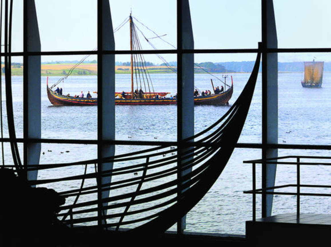 """June 13:1015a-4p:In the Footsteps of the Vikings A daytrip from Copenhagen to Roskilde - Join a day dedicated to the Vikings. An English-speaking guide will take you along to all the sights and tell you all you need to know.At the Viking Ship Museum in Roskilde you can really follow the Vikings footsteps, you will learn how they lived and get an insight into the their craftsmanship. At the museum you can also see the beautiful and impressive original ships they used to travel to faraway places.At the remarkable UNESCO listed Roskilde Cathedral, the famous Viking kings of Harald Bluetooth and Sweyn Forkbeard are buried alongside almost 40 Danish kings and queens. The Cathedral is one of the earliest examples of gothic architecture in Northern Europe and you will hear stories of how Sweyn Forkbeard conquered England as well as tales of Harold Bluetooth.You will not only follow in the footsteps of the Vikings, you will be at the cradle of Danish civilization in Lejre, one of the most important power centers during the Viking Era and Iron Age dating from 500-1000 AC and home to a unique complex of long houses. At Lejre Museum, located in the national park Skjoldungernes Land, you will learn about ferocious myths, and taste a glass of the legendary Viking drink mead, which legend has it """"he who drinks mead is ensured eloquence and knowledge""""."""