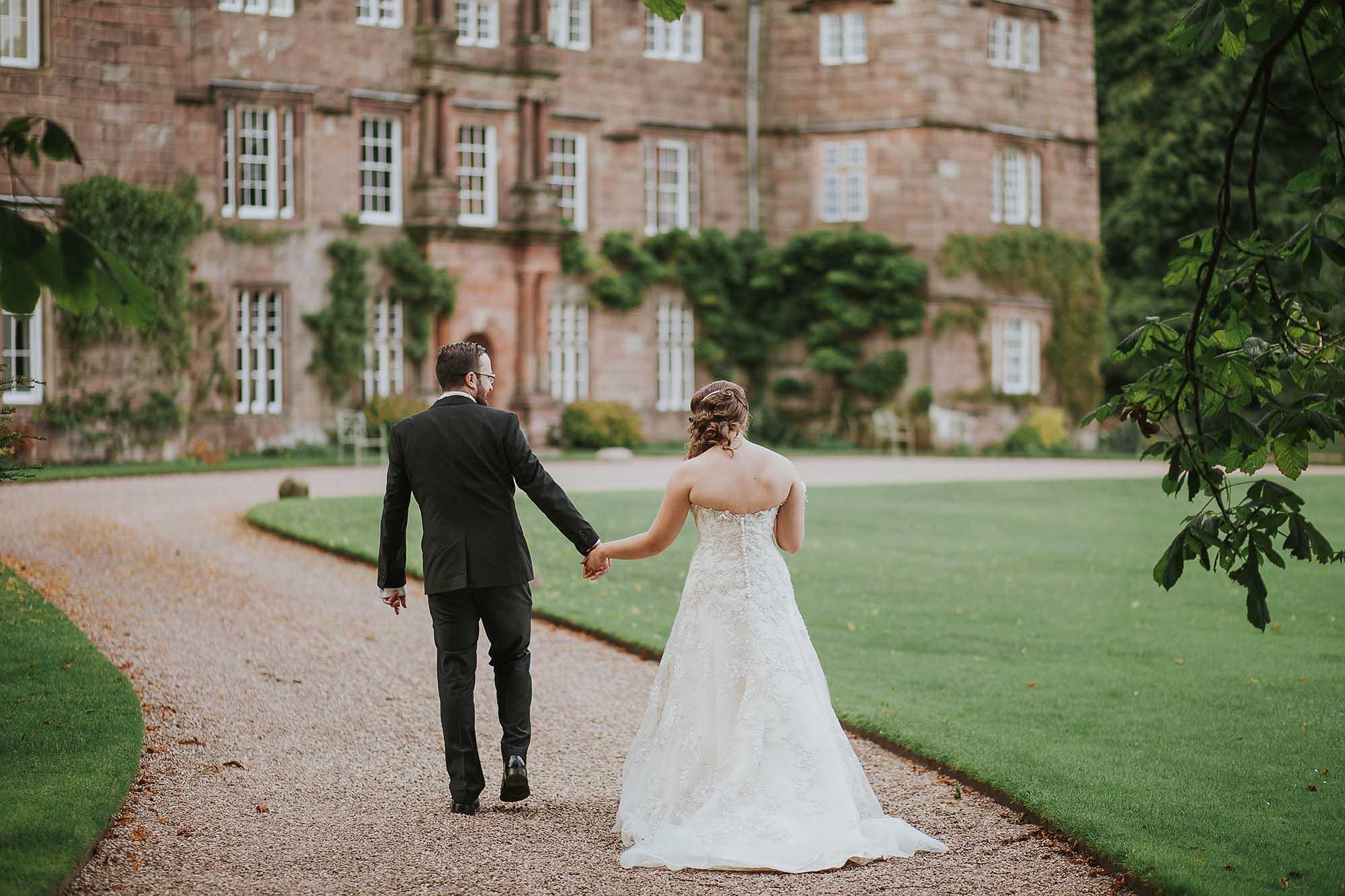 bride and groom walking outside Browsholme Hall and Tithe Barn