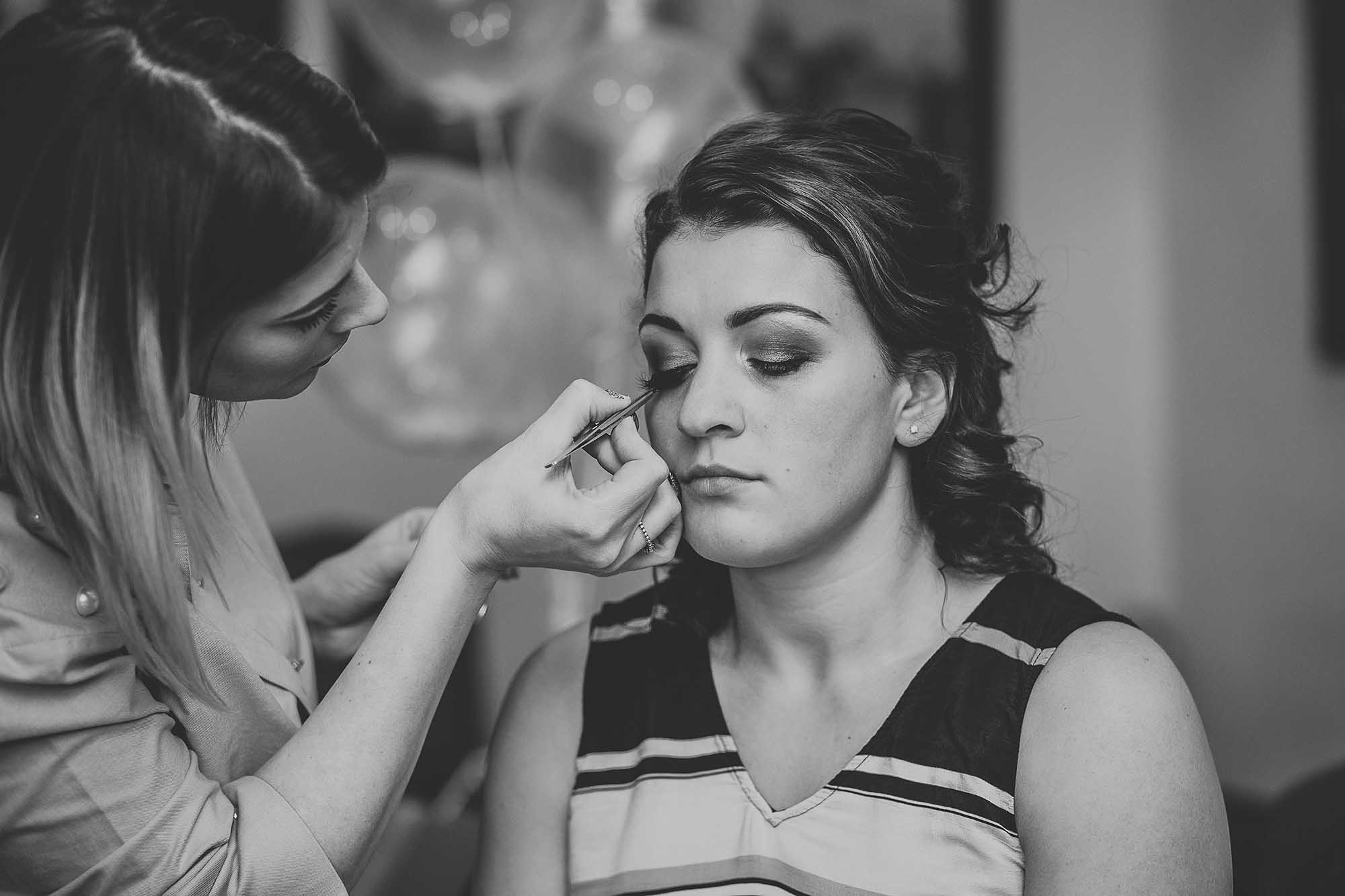 bridesmaid getting her makeup done at Holdsworth House