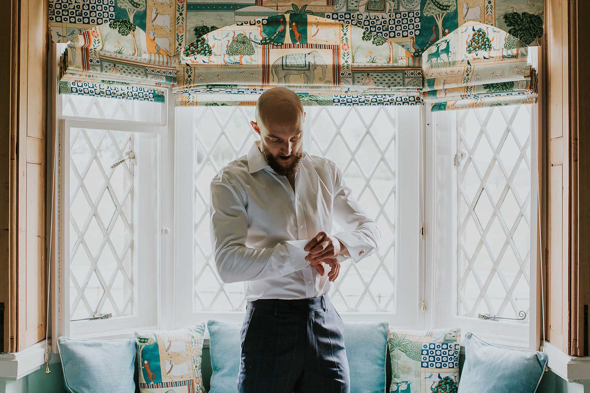 groom getting ready in a cottage at Combermere Abbey