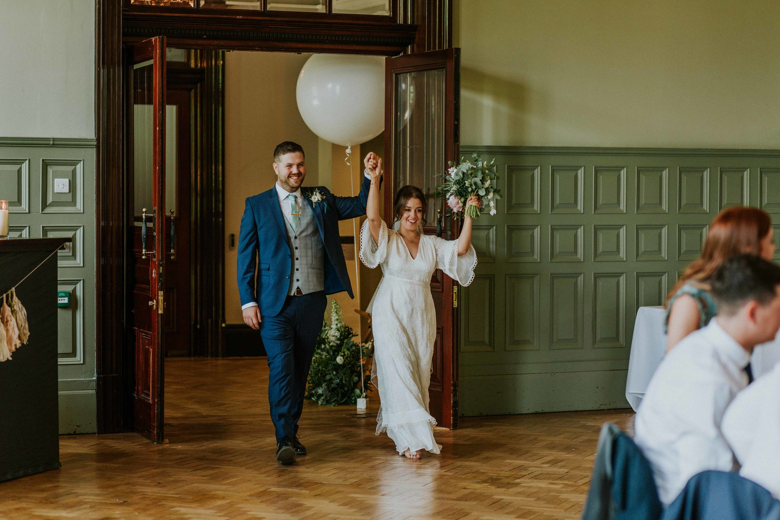 bride and groom walking into wedding venue at The Whitworth