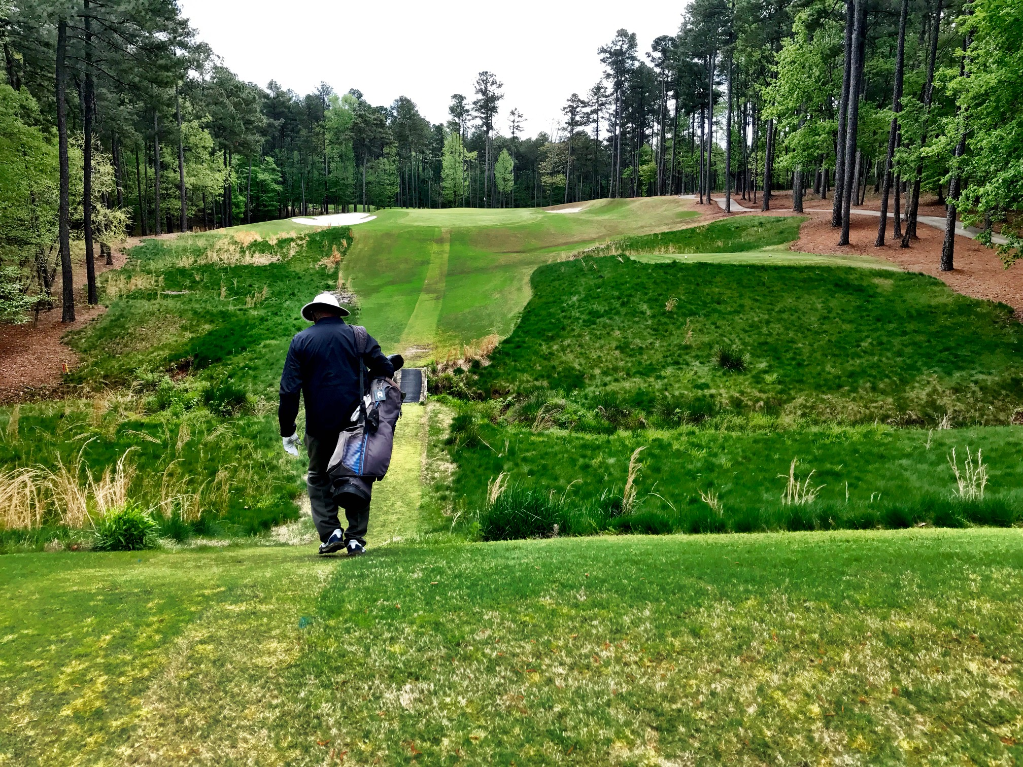 "Howard Lee walking off the seventh tee down one of the paths maintained for the benefit of walkers. ""I just think as long as someone my age can walk, it would be a sin not to do it,"" Lee says."