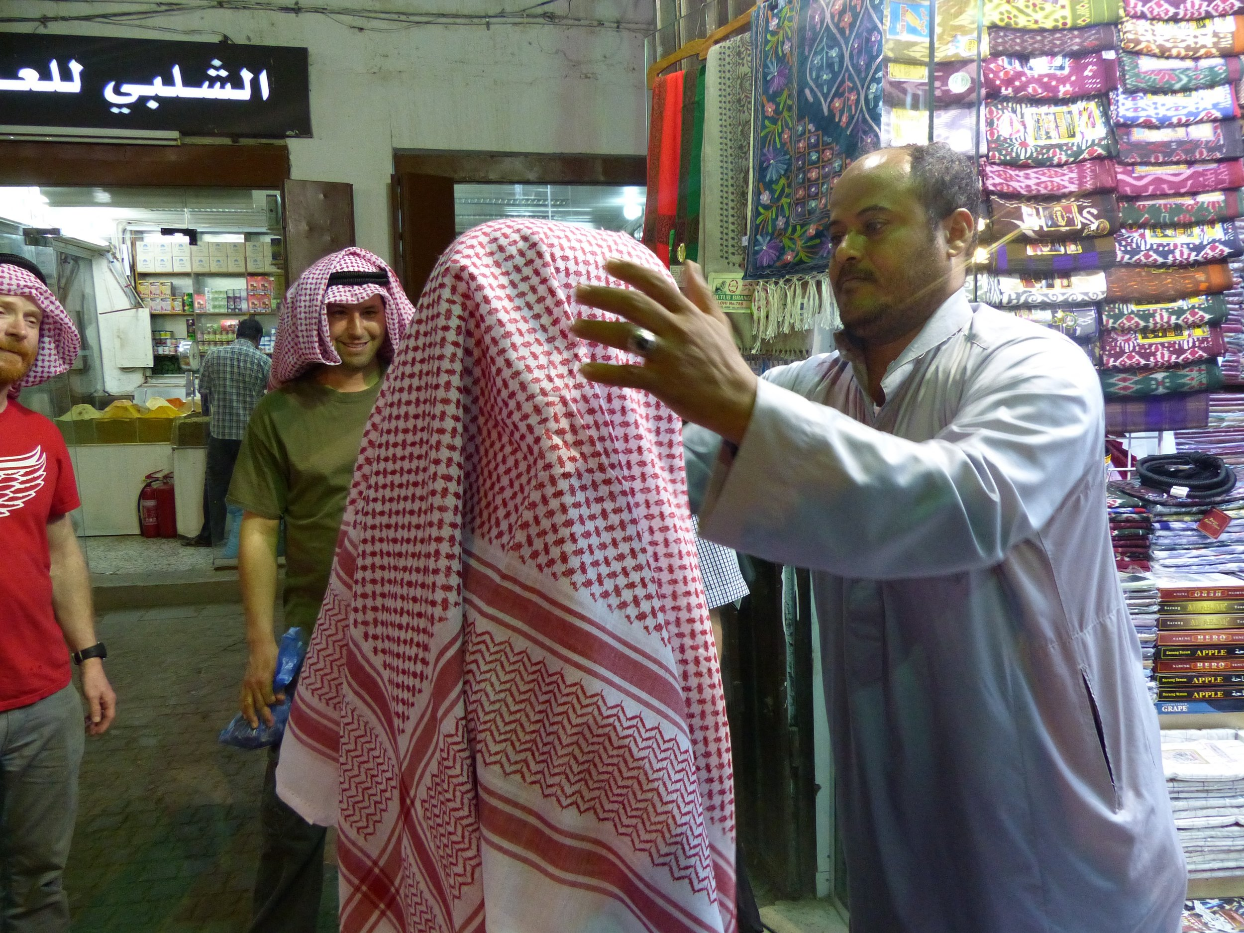 A local clothing merchant helps set us up with Keffiyeh.