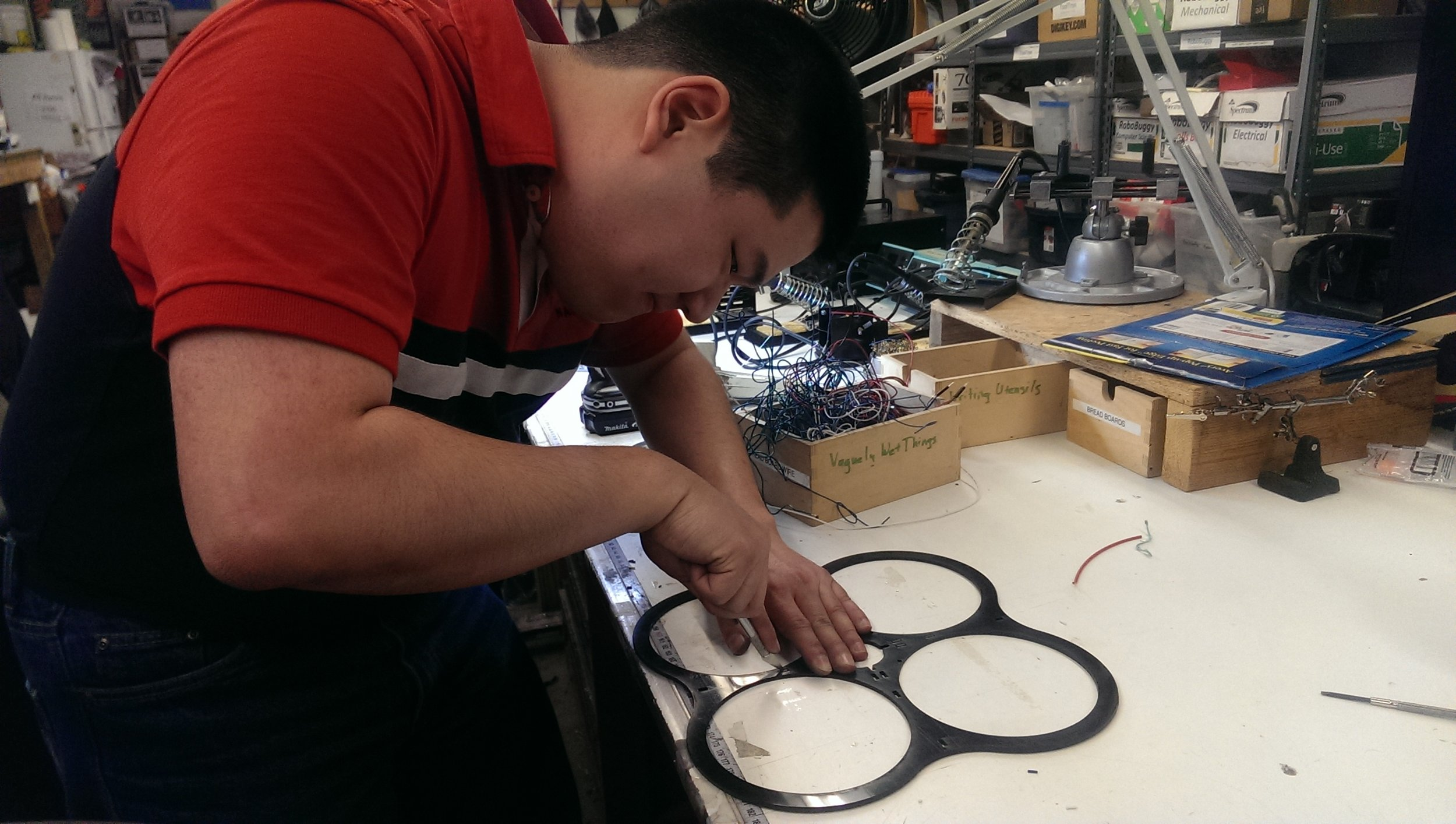 Student finalizing shape of laser cut frame