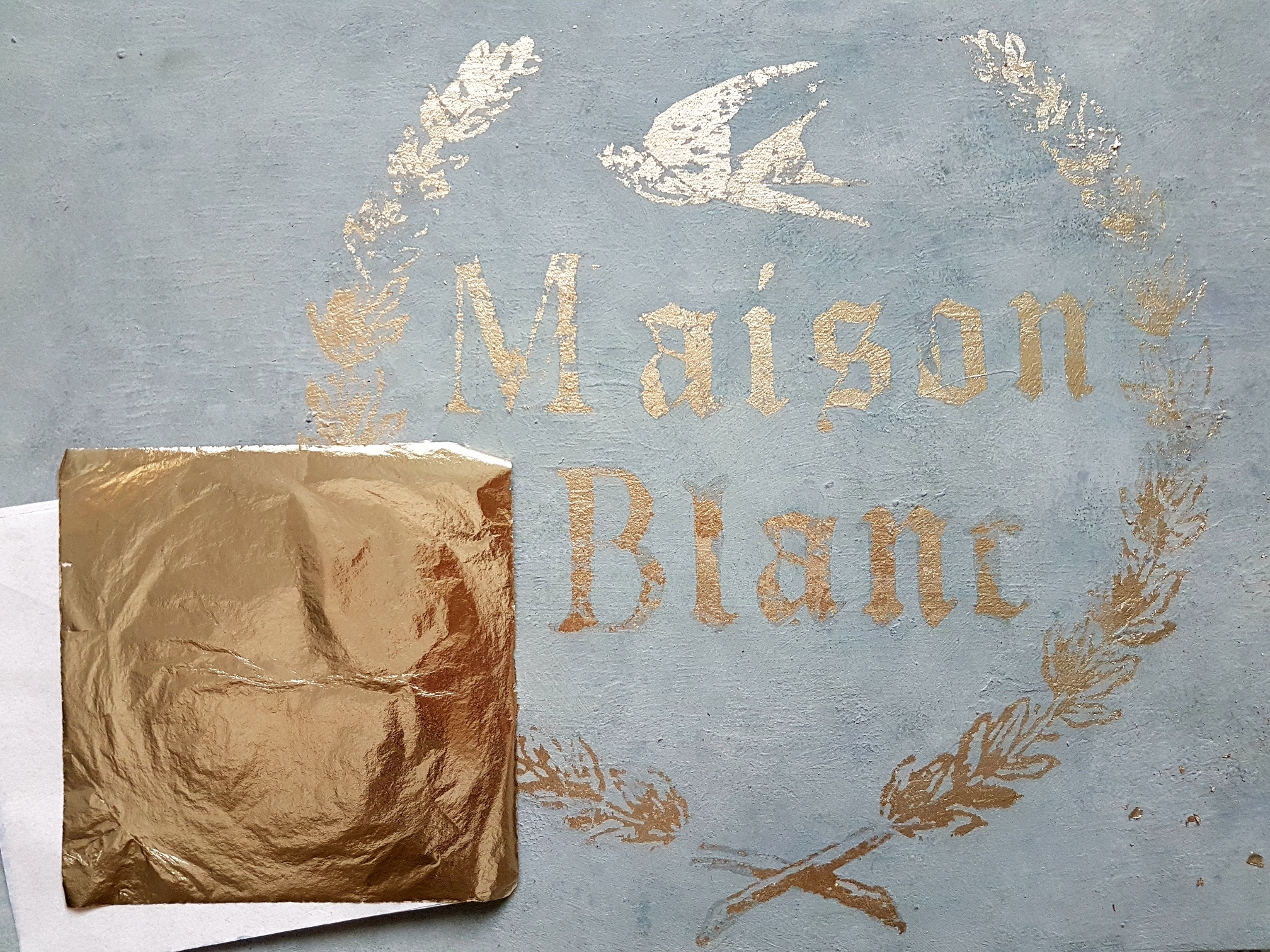 Stamp with gold leaf glue and add the gold leaf over the stamped images. For a vintage look, leave some areas bare.
