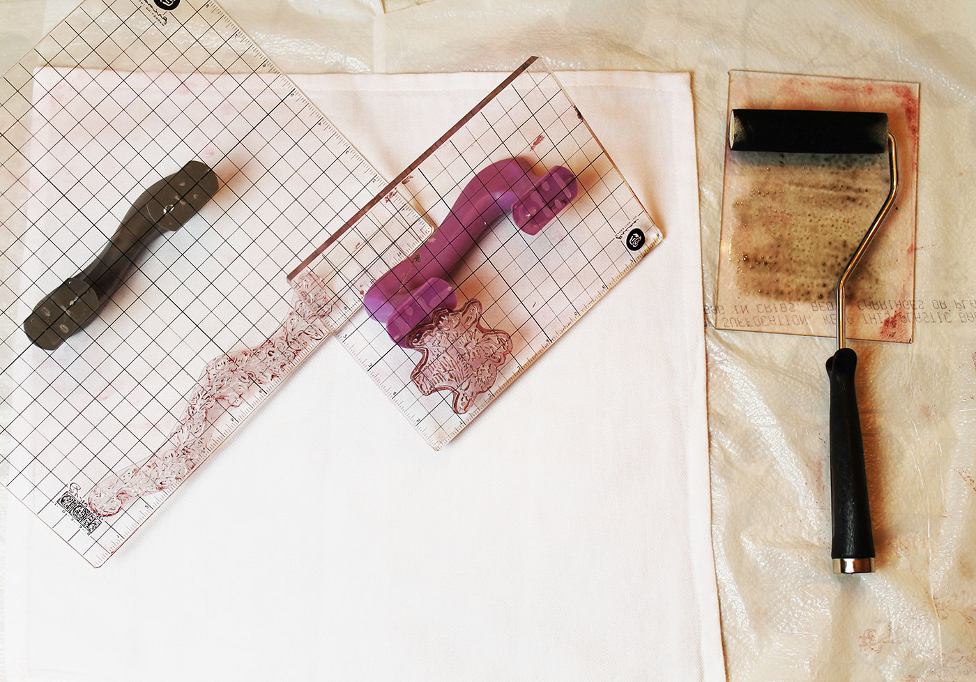 1: Protect your work surface with a trash bag or scrap fabric. Prepare your napkin by ironing out all the wrinkles for a nice smooth surface to stamp on and layout it out flat on a hard surface for best results. Add stamps to stamp blocks and add ink to your roller.