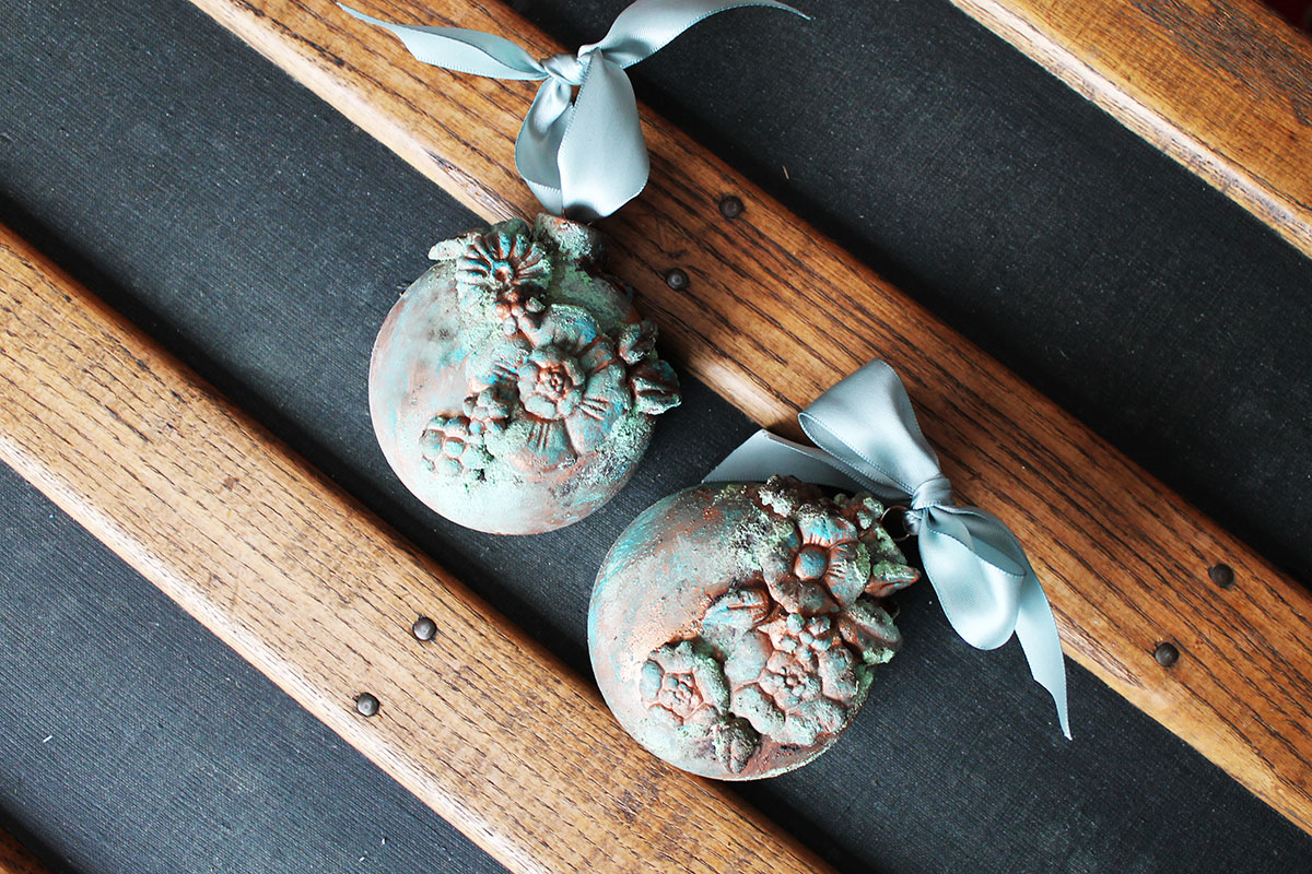 This year, we have seen so many DIYers creating ornaments for the holidays using the IOD moulds and a variety of art mediums with stunning results. So I decided to create a couple of my own ornaments using the Patina Pastes and I also created the same effect on another type of project so that you can get an idea of how it will look on another surface. The Patina Effect Pastes by Finnabair for Prima are so fun to use and the results are pretty awesome. They differ from other Patina mediums because they have the added texture within the pastes, giving the end result a more authentic look.