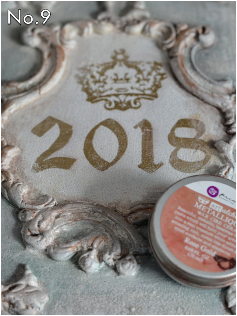 Paint with any color you wish! Add a dry brushed layer of white over the color to tone it down and antique it a bit. Then apply the Art Alchemy Metallique Wax by Finnabair to the designs. Here, Cat used Rose Gold. You can also mix or layer more than one wax color too!
