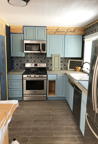 Fast forward-all cabinets were installed along with concrete countertops and appliances. We chose a dusty blue chalk style paint to paint over the bland white cabinets. We added two coats all together and let them dry for a few days before putting the doors and drawers back in place.