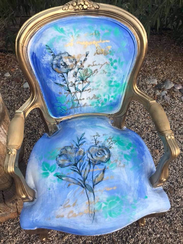 This is a better angle to see the hand painted florals. Aren't they gorgeous? Then she went over the patterns with some stenciling and spray paint to tie in the gold luster from the frame.  How amazing are these three art chairs? We hope you enjoyed today's post and it inspires you to create an art piece of your own!