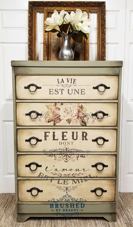 This chest of drawers was given an antique finish with a combination of colors, wax and the redesign transfer, L'amour Est Le Miel. The whole package is perfection! Brandy used Spanish Moss and Burlap paint colors along with a mixture of black and brown waxes all by Dixie Belle.