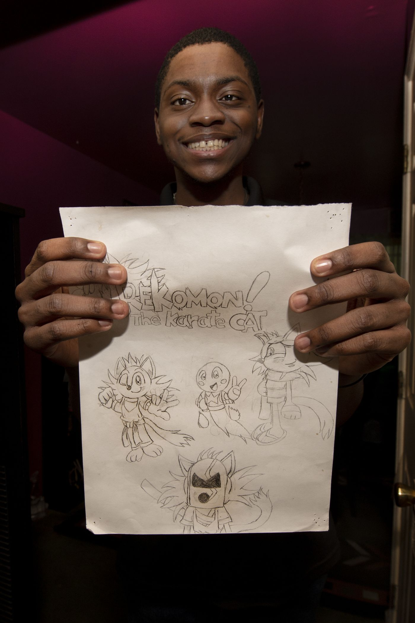 "JOSE F. MORENO / STAFF PHOTOGRAPHER Andrew Cambridge, smiles as he shows his drawings of ""Rekomon! The Karate Cat"" at his home in Willow Grove Pa."