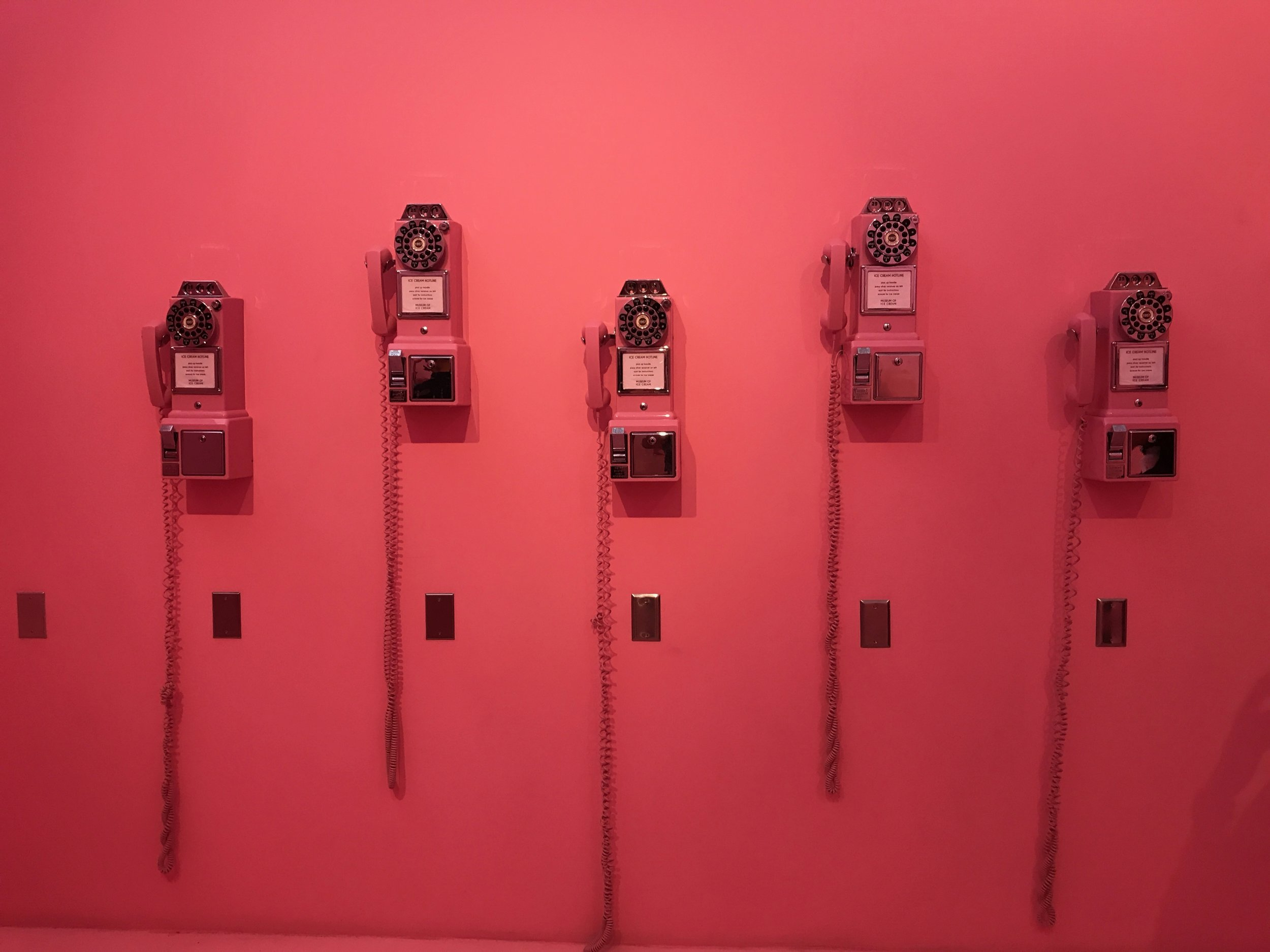 First room with pink walls and rotary phones