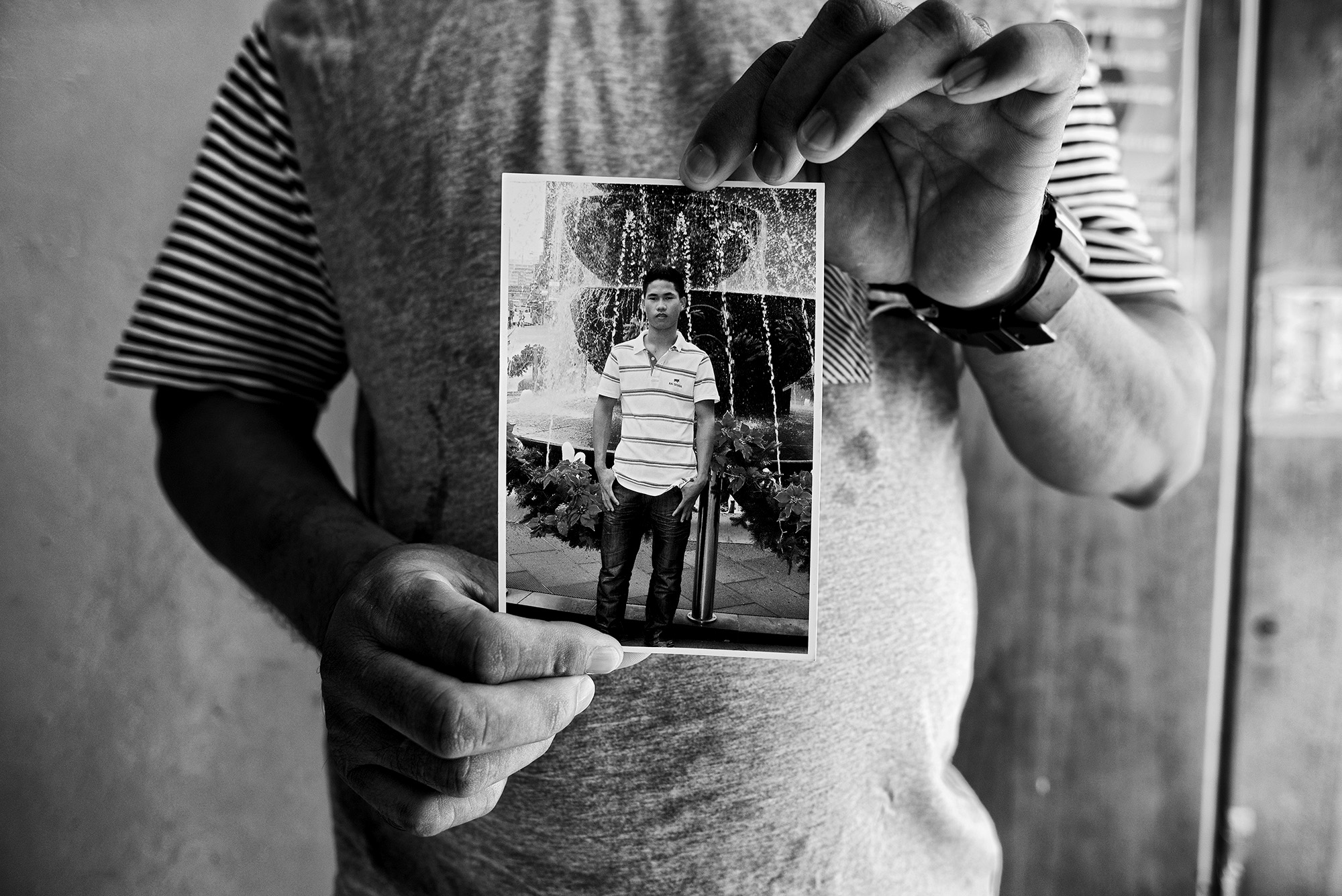 A 33-year-old man from the Chin community from Burma holds a photo of his 20-year-old nephew.