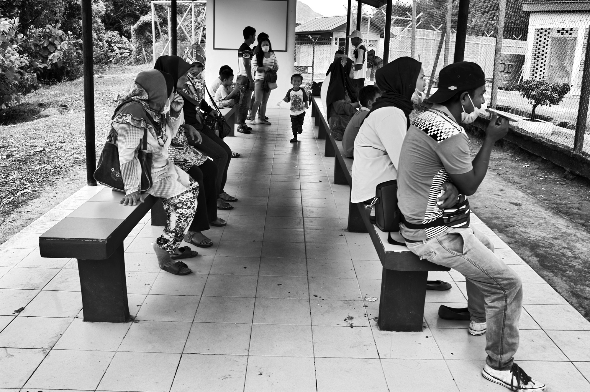 Families sit in the waiting area outside the Manggatal Detention Center in Kota Kinabalu, Sabah before being permitted to visit relatives in detention.