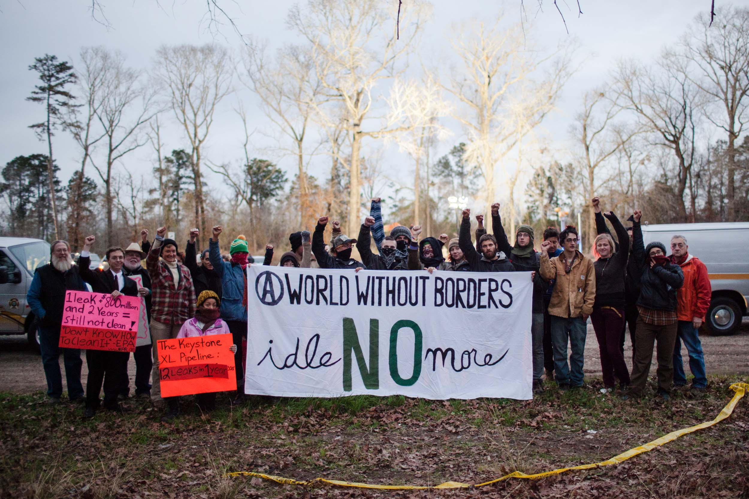 Environmental justice activists show a display of solidarity with the #IdleNoMore movement after a 2012 Tar Sands Blockade stand-off with local police, whose spotlights on the tree-sit can be seen behind the group.
