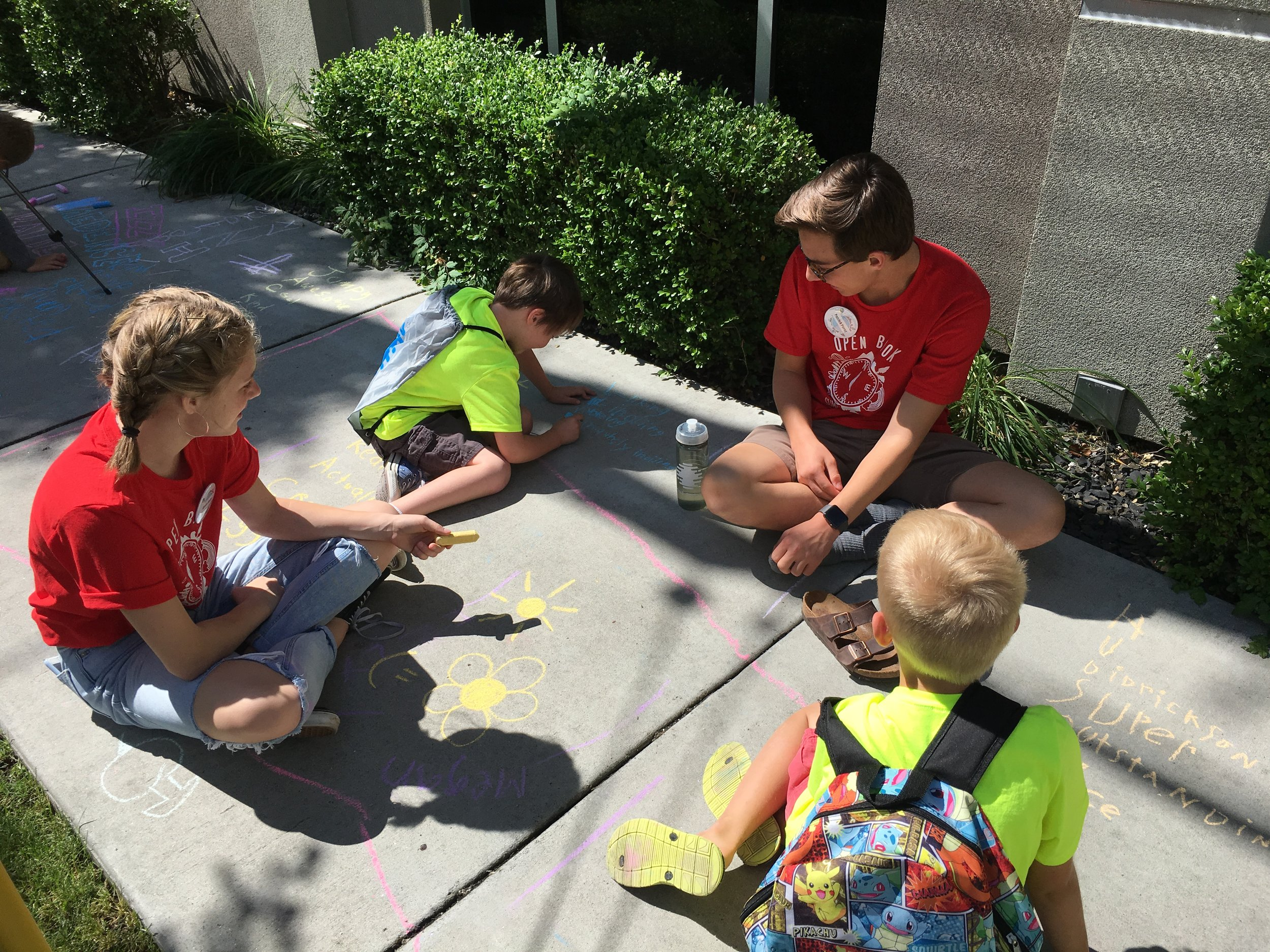 In Open Book Adventures, One Stone's longest running Project Good program, teenage guides are paired with first and second grade buddies to encourage a love of reading and writing. Pictured here, buddies practice handwriting skills.