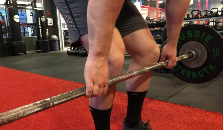 Move the knees out of the way as you drive the barbell off the floor