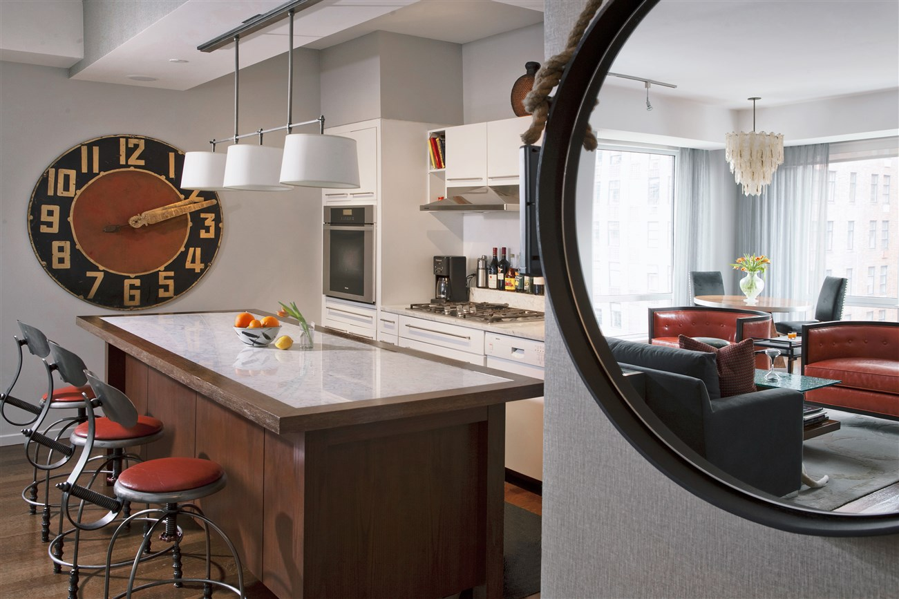 Kitchen area with island bar style bar and big wall clock