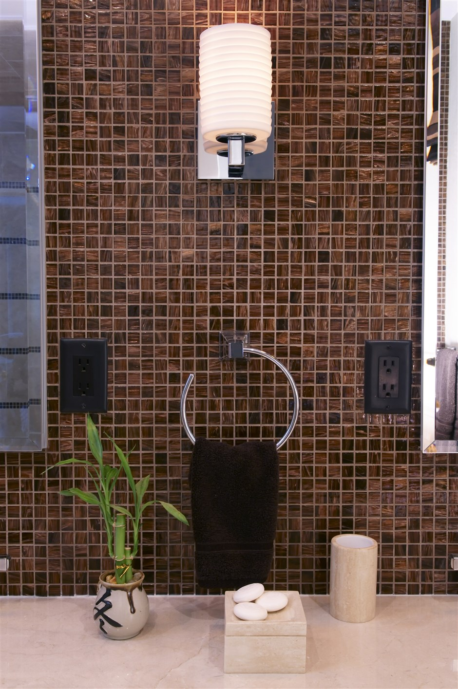 Sink portion of bathroom with indoor plant and stylish lamp on the wall