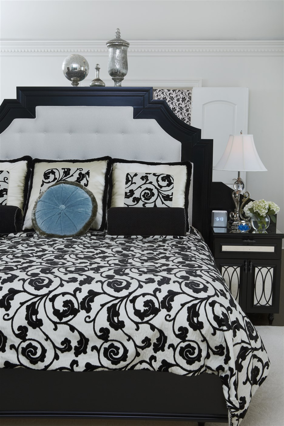 Bed with white headboard beside night lamp