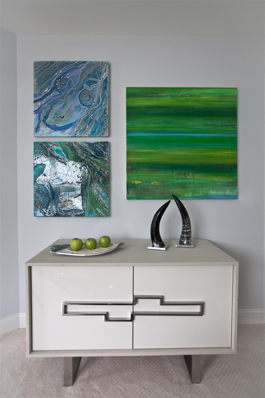 White cabinet and three abstract paintings on the all