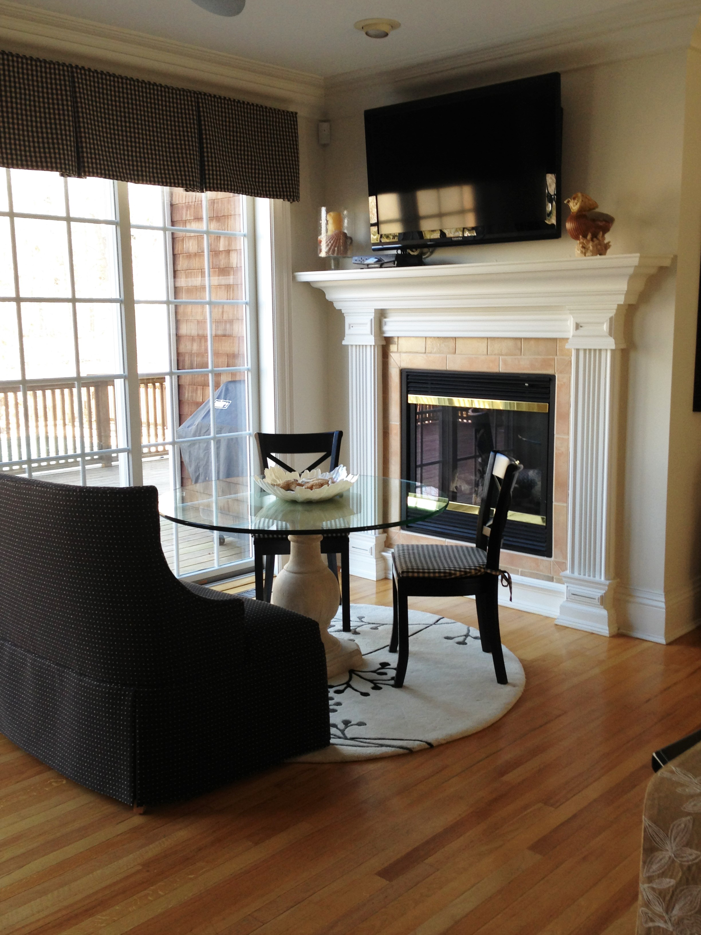 Glass round table for two in front of fireplace