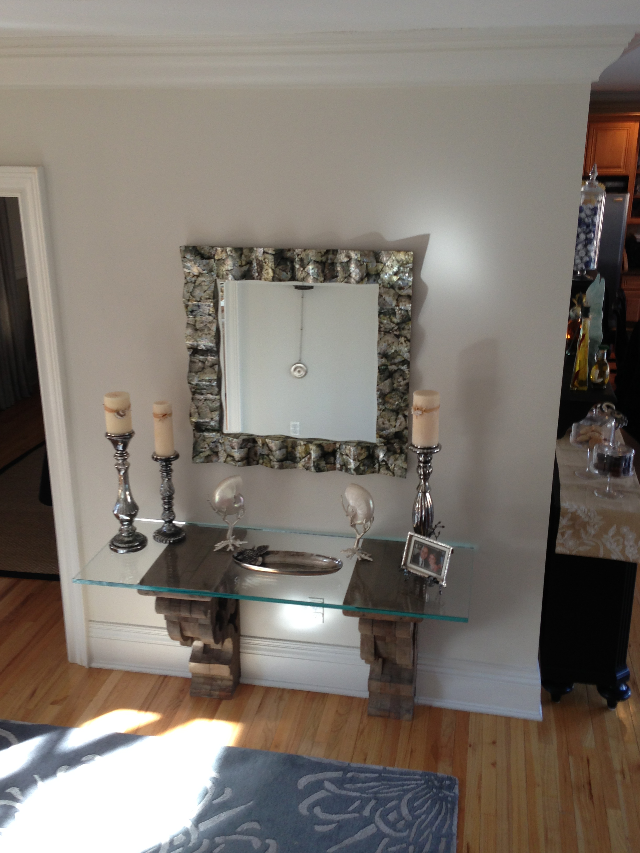 Glass table with decorations on top and mirror on the wall