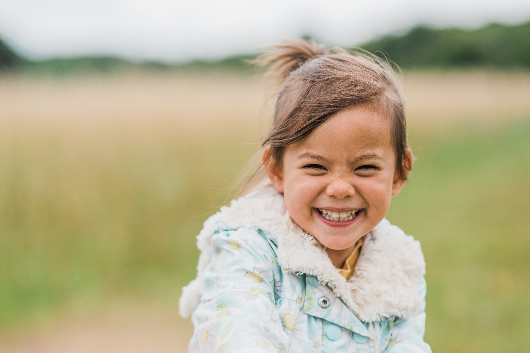 Girl smiling and running in field Cotswolds Child  Photographer.jpg