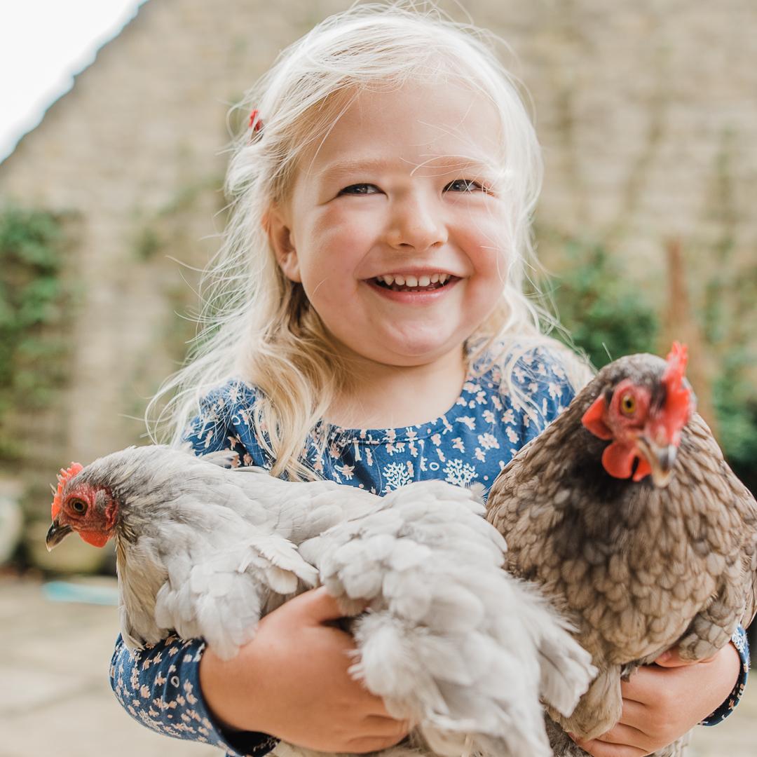 Little Girl hugging chickens Cheltenham Child Photographer.jpg