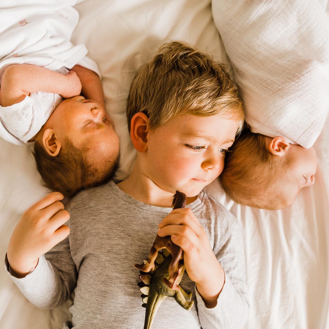 Cute Toddler boy with newborn twins in home photoshoot- cheltenham family photographer.jpg