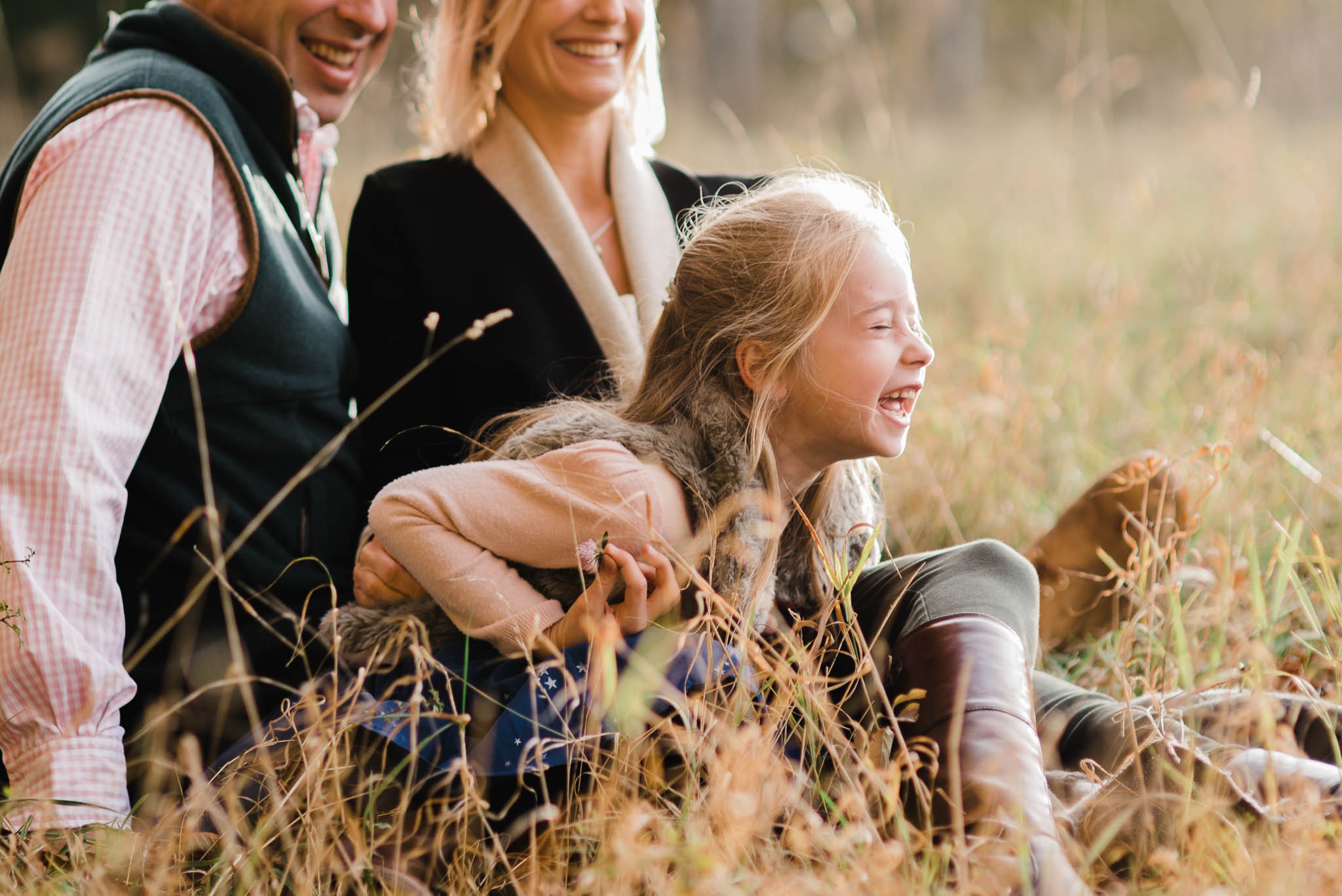Family of three lauging in fiekd- Cotswold Family Photoshoot.jpg