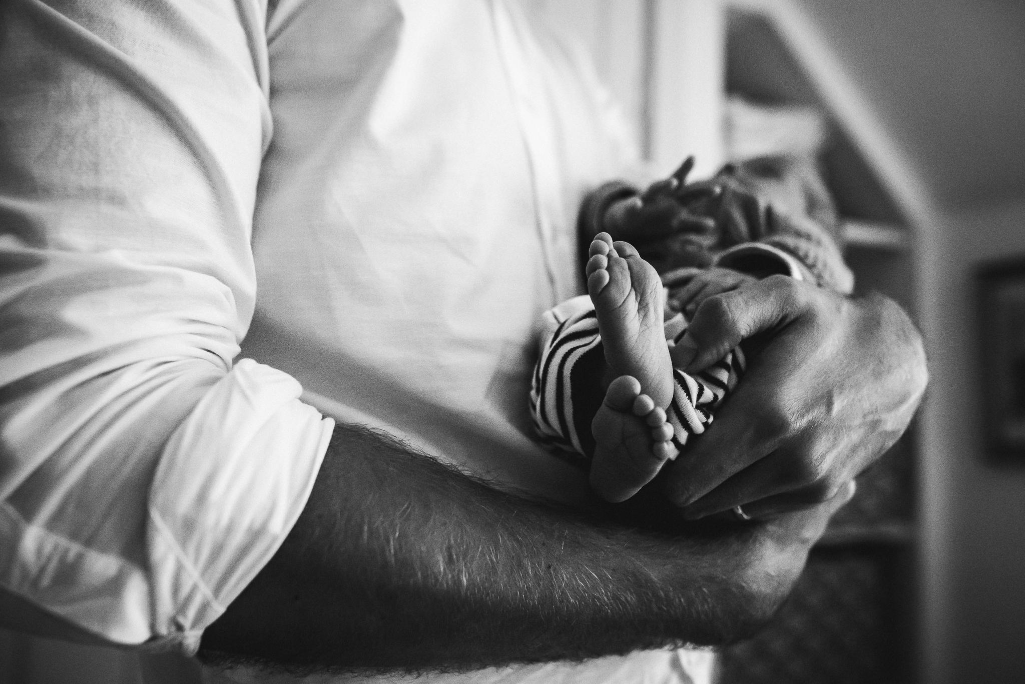 Newborn baby toes held in fathers arms Cheltenham Newborn Photographer.jpg