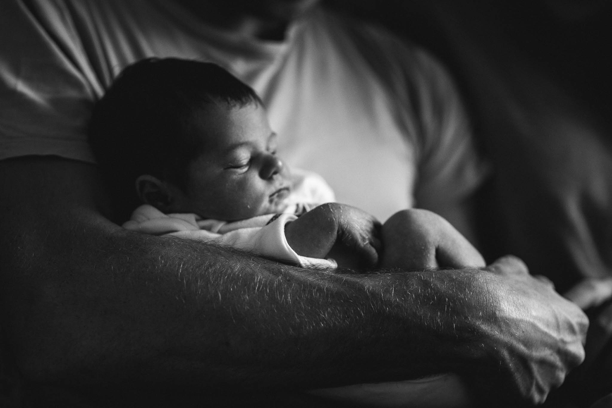 Newborn baby sleeping in dads arms Cheltenham Newborn Photography.jpg