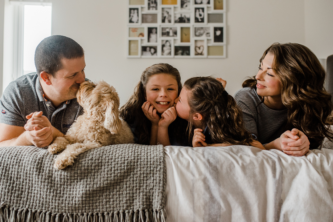 Happy family of four in bedroom with dog