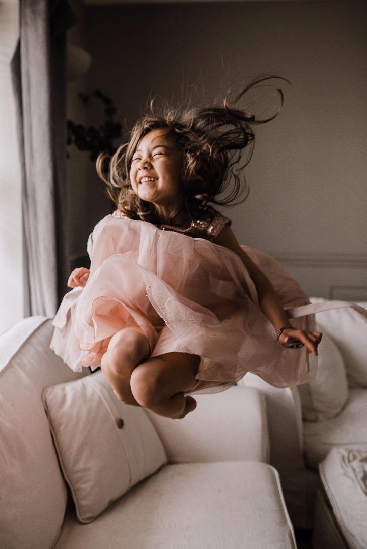 Girl jumping on sofa in a pretty dress Cheltenham Child  Photographer.jpeg