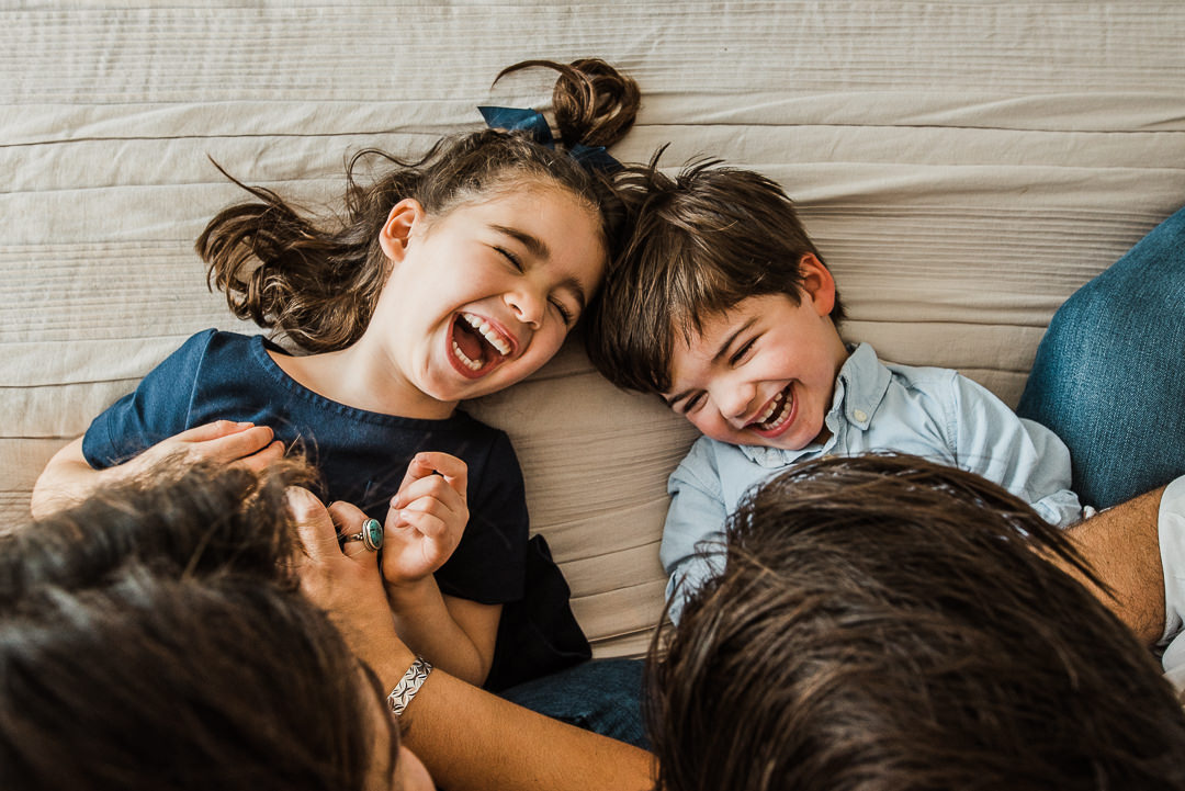 Children giggling on bed tickles