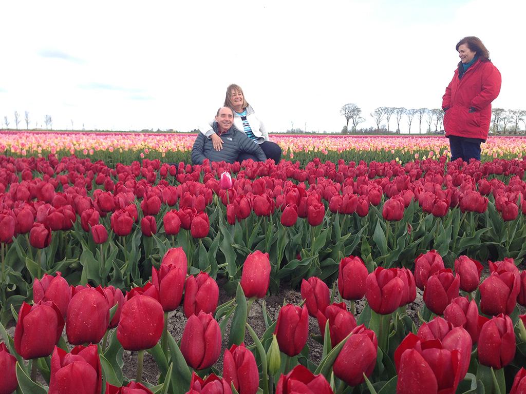 Three of last year's happy guests posing at one of tulip farms near Keukenhof Gardens.