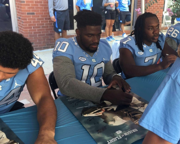 """Junior linebacker Andre Smith (10) signs a UNC football poster Saturday at the """"Meet the Heels"""" event."""
