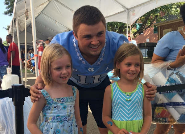 """Sophomore quarterback Nathan Elliott poses with two young fans at """"Meet the Heels"""" on Saturday."""