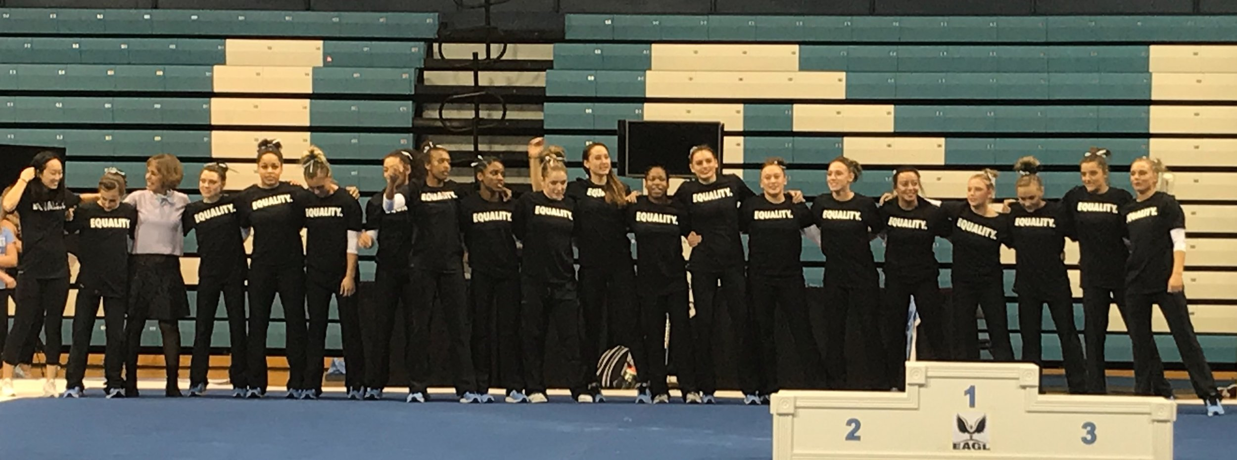 """UNC gymnasts wearing """"EQUALITY."""" T-shirts celebrate a win over Temple University, and inclusion and diversity, with Chancellor Carol Folt   Photo by Bryce Lapping"""