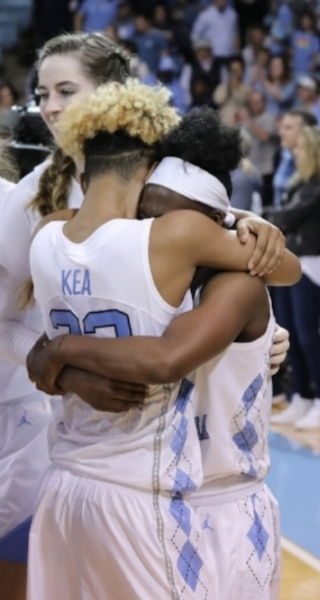 Paris Kea (22) and Jamie Cherry (10) embrace after Sunday's overtime win over Duke. | Photo by Caleb Jones