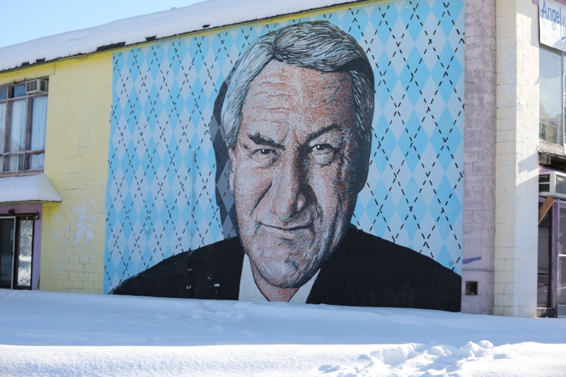 On the side of a gas station in Chapel Hill, a mural of Dean Smith watches over those who pass by. It's a tribute fitting of a man who'd never have wanted it. | Photo by Caleb Jones