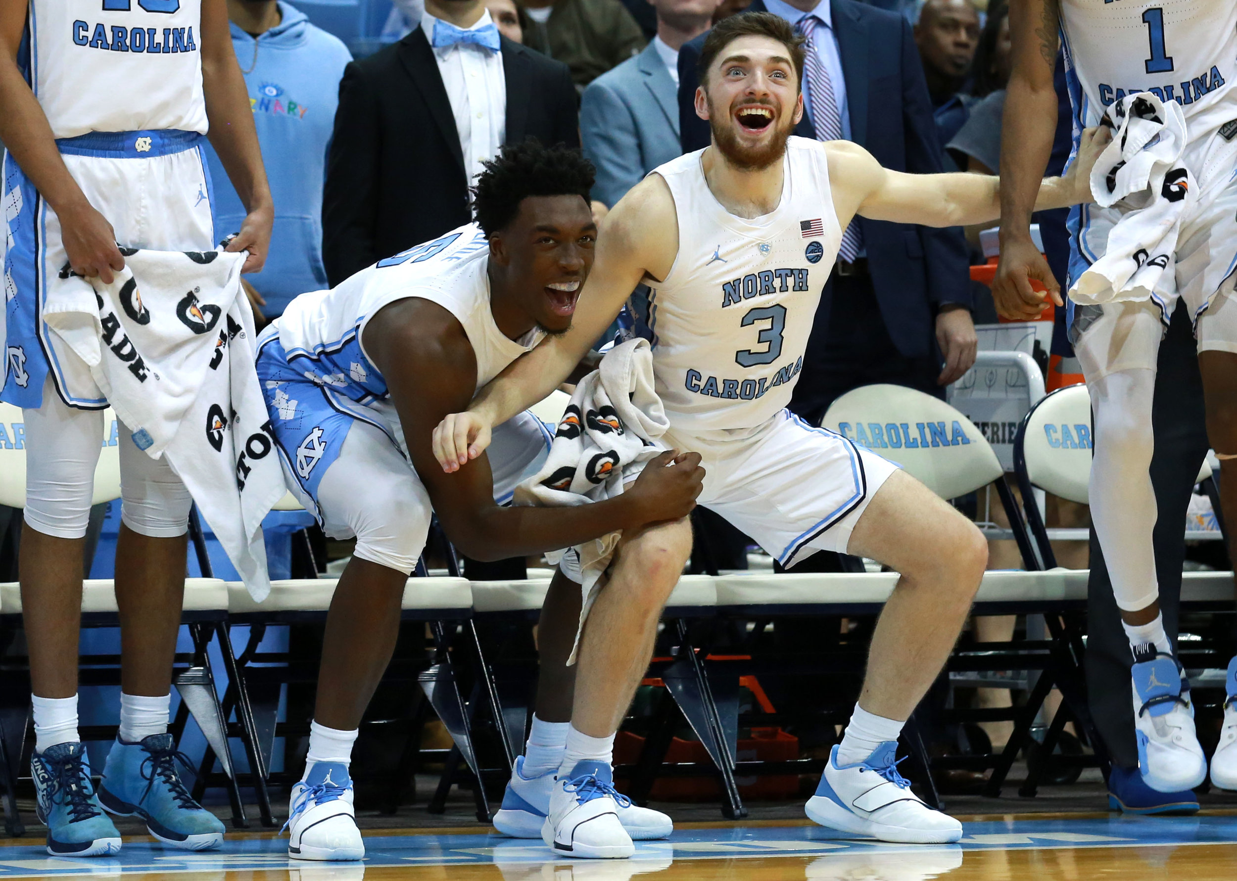 Nassir Little and Andrew Platek get low and celebrate on the Tar Heel bench.   Photo by Alex Kormann